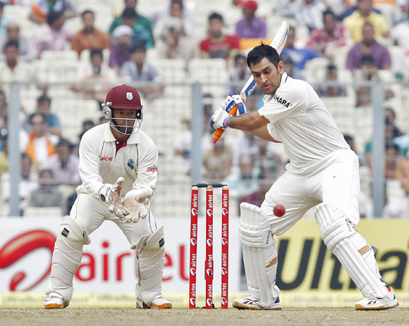 Dhoni (R) plays a shot as West Indies' wicketkeeper Carlton Baugh watches