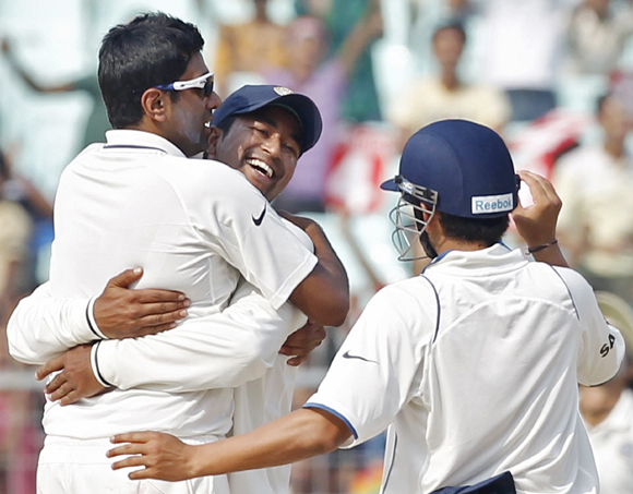 Ravichandran Ashwin (L) is congratulated by Pragyan Ojha as Gautam Gambhir (R) watches