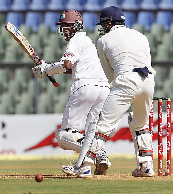 Kraigg Brathwaite plays a shot past India captain and wicket keeper Mahendra Singh Dhoni