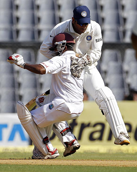 Dhoni (right) collides with the West Indies' Adrian Barath