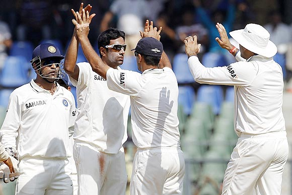 Ravichandran Ashwin (centre) celebrates with teammates after dismissing Barath