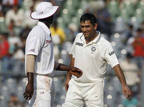 MS Dhoni speaks to Darren Sammy during the fifth day of the third Test