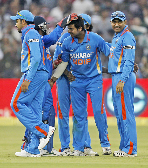 India's Suresh Raina (C) celebrates with teammates after taking the wicket of West Indies' Darren Bravo during their first one-day international match in Cuttack