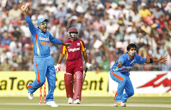 India's Vinay Kumar (R) and his teammate Rohit Sharma (L) appeal successfully for the wicket of West Indies' Adrian Barath during their first one-day international match in Cuttack
