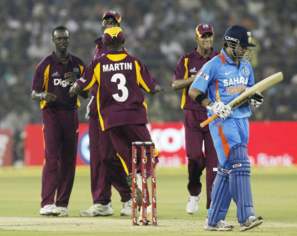 West Indies' Kemar Roach (L) celebrates with teammates after dismissing India's Gautam Gambhir (R) during their first one-day international cricket match in Cuttack