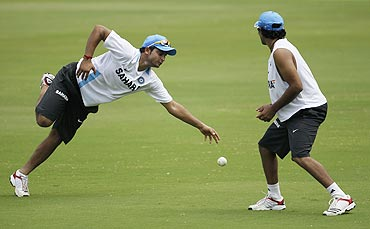 Suresh Raina (left) dives to take a catch as teammate Ravindra Jadeja watches
