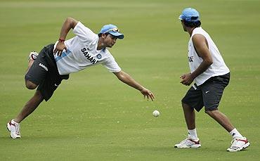 Suresh Raina (left) dives to take a catch as teammate Ravindra Jadeja watches