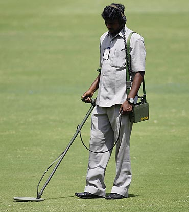 A security official uses a metal detector on the field