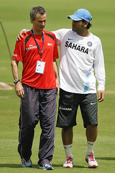 India's captain Mahendra Singh Dhoni (right) talks to umpire Billy Bowden as he takes a break from practice on Thursday