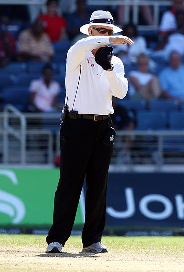 Umpire Tony Hill signals for a referral