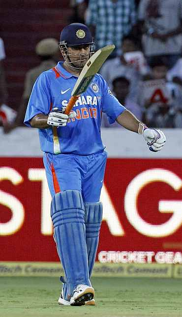 MS Dhoni raises the bat after getting to fifty