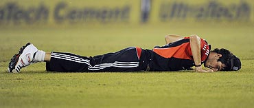 England's Steven Finn lies on the ground after a misfield