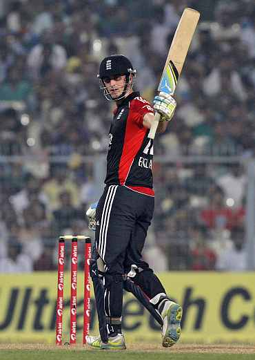 Craig Kieswetter raises his bat after completing a half-century