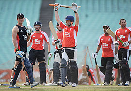 England captain Graeme Swann celebrates after hitting a six during a nets session at Eden Gardens on Friday