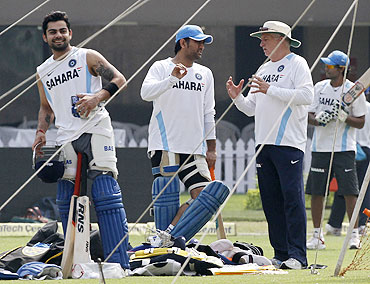 India captain Mahendra Singh Dhoni (centre) listens to coach Duncan Fletcher, as teammate Virat Kohli (left) smiles, during a practice session ahead of their Twenty20 international against England