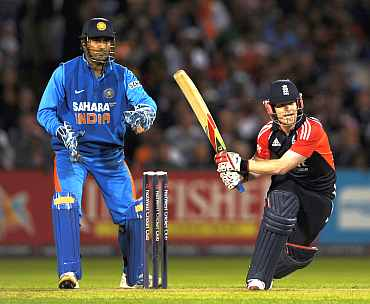 Eoin Morgan plays a sweep shot as MS Dhoni was looks on
