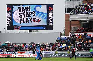 The players leave the field as rain stops play during the NatWest One Day International between England and India
