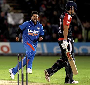 Virat Kohli celebrates after picking up the wicket of Alastair Cook