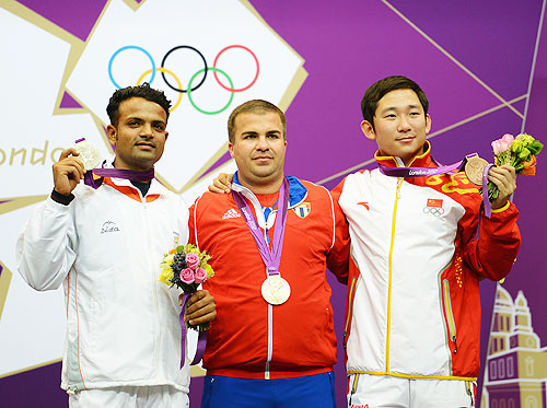 Gold medallist Leuris Pupo (centre) of Cuba, silver medallist Vijay Kumar of India and bronze medallist Feng Ding of China pose on the podium