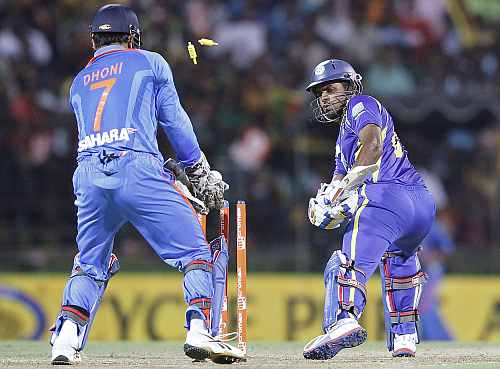 Sri Lanka's Lahiru Thirimanne (R) is bowled out by India's Ravichandran Ashwin during the Twenty20 match