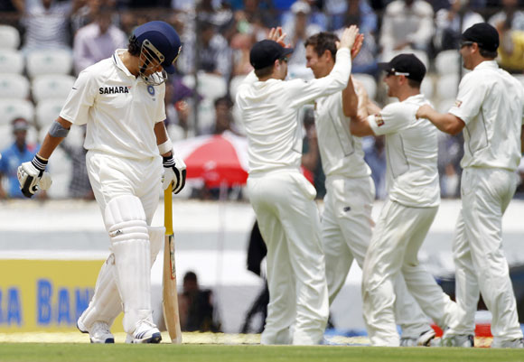 India's Sachin Tendulkar (L) walks back to the pavilion after being dismissed as New Zealand's Trent Boult (C) celebrates with teammates during the first day of their first test cricket match in Hyderabad