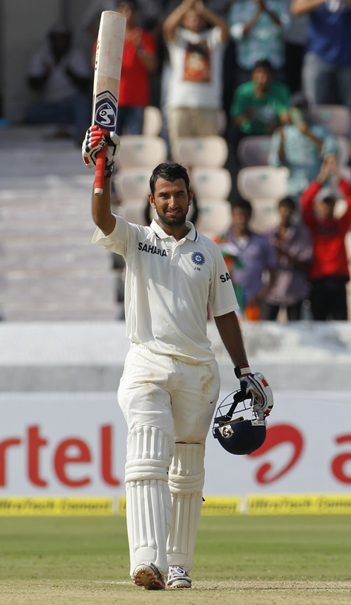 Pujara raises his bat to celebrate scoring a century