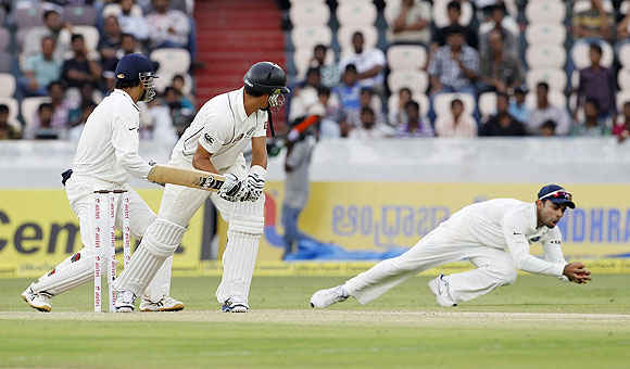 New Zealand's captain Ross Taylor (centre) watches as India's Virat Kohli (right) dives to takes a catch to dismiss him off the bowling of R Ashwin