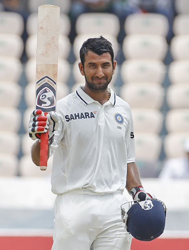 India's Cheteshwar Pujara raises his bat to celebrate scoring 150 runs during the second day of their first test cricket match against New Zealand in Hyderabad