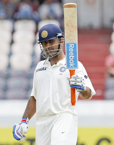 India's captain Mahendra Singh Dhoni raises his bat to celebrate scoring 50 runs