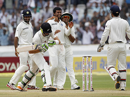 India's Pragyan Ojha (centre) celebrates with teammates after taking the wicket of New Zealand's Martin Guptill