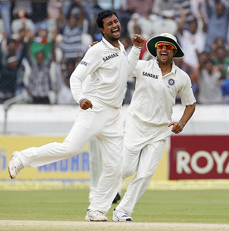 India's Pragyan Ojha (left) jumps as he celebrates with teammate Suresh Raina after taking the wicket of New Zealand's Brendon McCullum