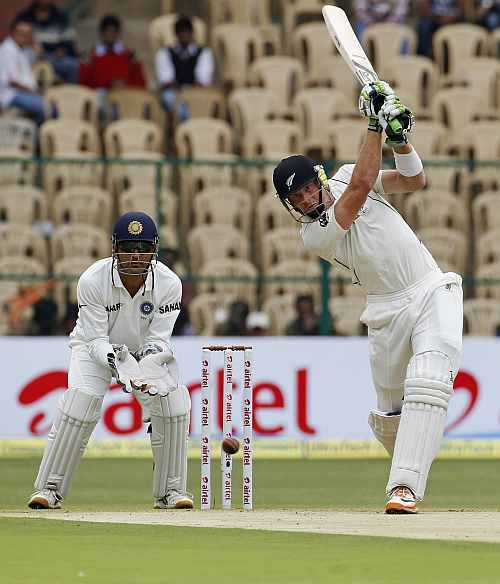 New Zealand's Martin Guptill hits a shot as MS Dhoni watches on during the first day of their second Test match in Bangalore
