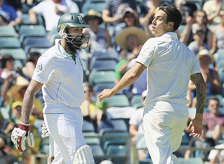 Australia's Mitchell Johnson (right) looks back as South Africa's Hashim Amla (left) is dismissed at the WACA