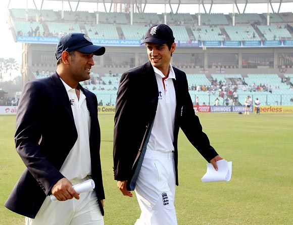 India captain Mahendra Singh Dhoni walks out for the toss with England's captain Alastair Cook
