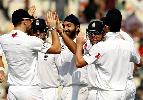 Monty Panesar celebrates with team-mates after taking the wicket of Cheteshwar Pujara