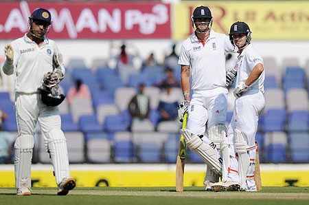 Kevin Pietersen and Jonathan Trott look on as MS Dhoni sets the field