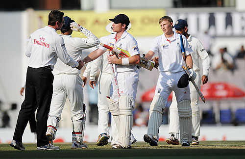 Ian Bell of England and Joe Root greet the Indian team and the umpires after the match en