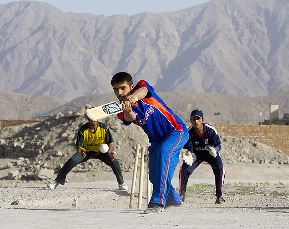 A batsman tries to hit the ball during a neighborhood cricket game