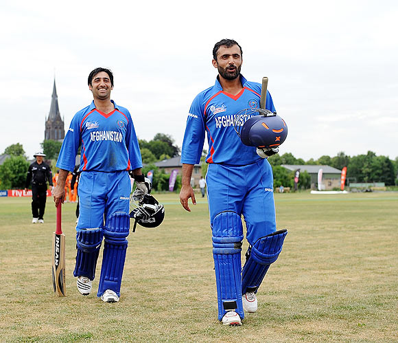 Nowroz Mangal (right) and Asghar Salakhail of Afghanistan leave the field after beating Netherlands during the ICC World Cricket League Division One match