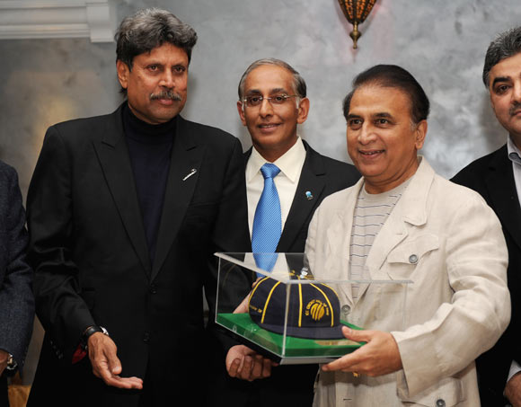 Former Indian cricketer Sunil Gavaskar (R) is presented with his ICC Hall of Fame cap by Kapil Dev (L) and ICC Chief Executive Haroon Lorgat
