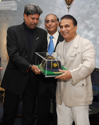 Former Indian cricketer Sunil Gavaskar (R) is presented with his ICC Hall of Fame cap by Kapil Dev (2nd L) and ICC Chief Executive Haroon Lorgat