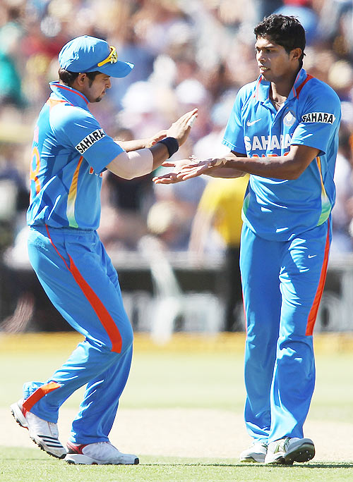 Umesh Yadav (right) of India celebrates after getting the wicket of Peter Forrest