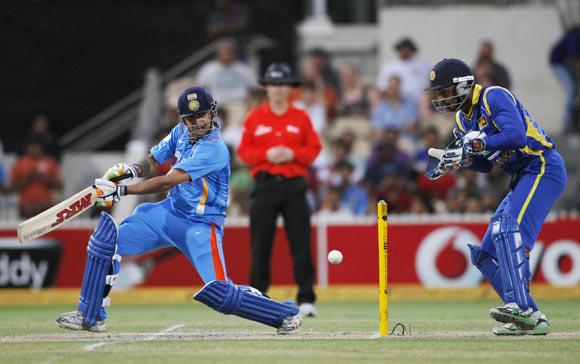 Gautam Gambhir (L) plays a shot as wicket keeper Kumar Sangakkara looks on