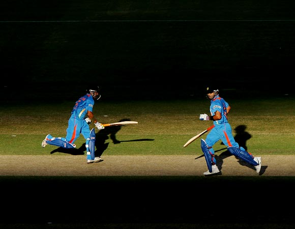 Gautam Gambhir (left) and Virat Kohli run between the wickets