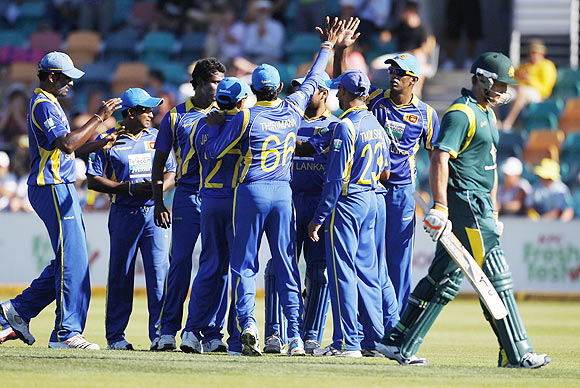 Sri Lankan players celebrate the dismissal of Forrest (right) as he walks of the field