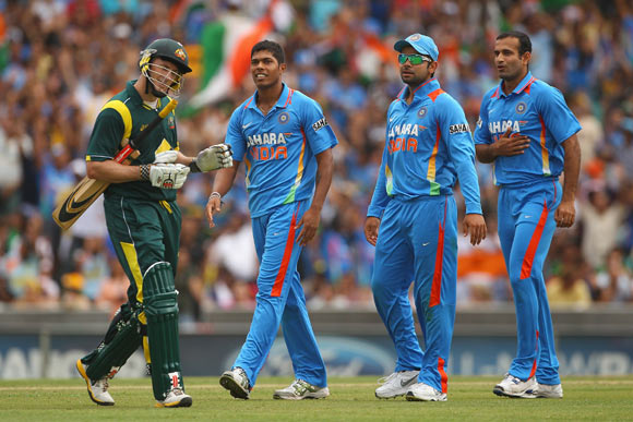 David Hussey of Australia walks after the field after being dismissed by Umesh Yadav of India (L) during the One Day International match
