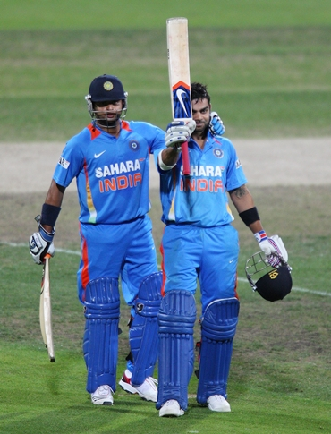 Kohli gets a pat from Suresh Raina after completing a hundred