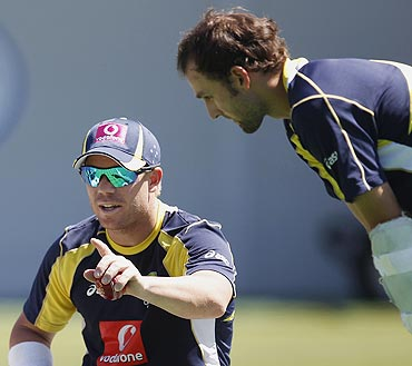 Australia's Nathan Lyon (right) chats with teammate David Warner in the nets during a practice session in Sydney on Monday