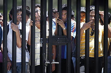 Indian cricket fans peer through the bars of a fence next to the nets area to try and catch a glimpse of the Indian cricket team members during a practice session on Monday