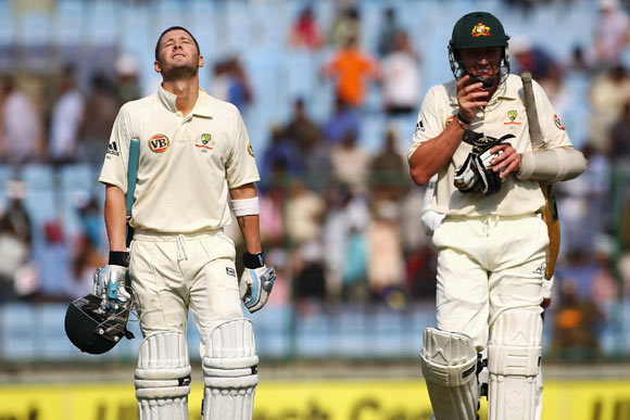 Michael Clarke (L) of Australia shows his relief alongside Brett Lee after reaching his century during day four of the Third Test match between India and Australia in Ferozshah Kotla